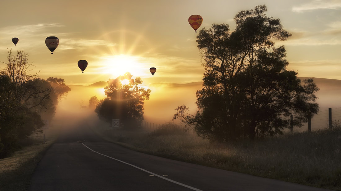 Five hot air balloons floating approximately 50-100 meters in the air. There is a sunrise in the background with fog and trees in the foreground.